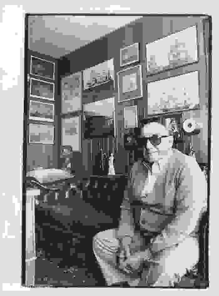 Eugène Colson auf einem Sofa vor einer Wand voller Bilder