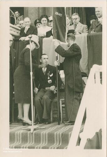 Marcel Louette sitzt auf einem Stuhl am Mikrofon und hat 2 Personen vor sich