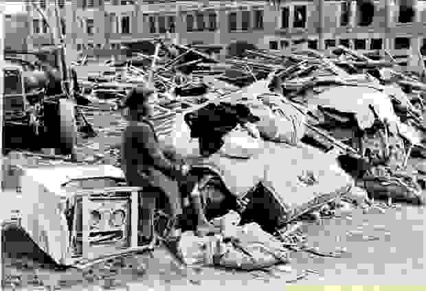 Eine Frau sitzt nach dem Bombenangriff auf Mortsel zwischen den Trümmern auf einem Gerät